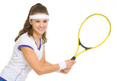 Smiling female tennis player ready to hit ball Royalty Free Stock Images