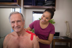 Free Smiling Female Therapist Applying Elastic Therapeutic Tape On Shoulder Of Shirtless Senior Male Pati Royalty Free Stock Image - 96123216