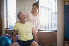 Smiling female therapist looking at senior male patient against window Stock Photography