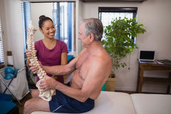 Smiling female therapist looking at shirtless male patient holding artificial spine Stock Photography
