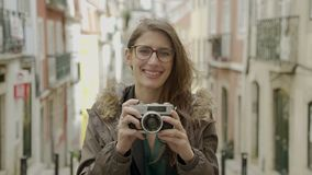 Smiling female tourist looking at camera while standing on street stock video footage