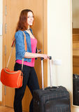 Smiling female tourist with luggage near door in home Royalty Free Stock Photography