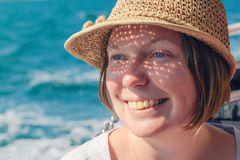 Smiling female tourist with straw hat at seaside Stock Image