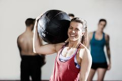 Smiling Female Trainer Carrying Medicine Ball Stock Image