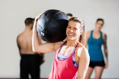 Smiling Female Trainer Carrying Medicine Ball Royalty Free Stock Photo