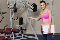 Smiling female trainer with clipboard pointing toward lat machine in gym Royalty Free Stock Photo