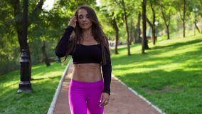 Smiling female trainer in short sport top walking in the park after intensive training. Fit healthy sport woman stock video
