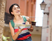 Smiling female traveler walking with map and bag in town Royalty Free Stock Photos