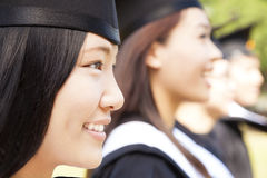 Smiling female university graduate  with classmates. Close-up smiling female university graduate  with classmates Stock Image