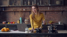 Smiling female use computer and stirs the sauce. Young woman cooking dinner and reading recipe. Adult lady using internet on pc in the kitchen. Caucasian model stock footage