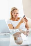 Smiling female using a cellphone sitting Stock Photos