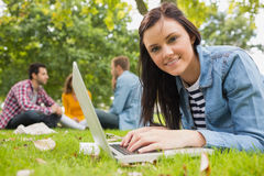 Smiling female using laptop with other students in park Royalty Free Stock Image