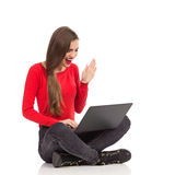 Smiling female usng laptop and waving hand. Smiling beautiful girl sitting on the floor with legs crossed, using laptop and waving hand. Full length studio shot Royalty Free Stock Images