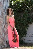 Smiling female violinist in long pink dress outside Stock Photography