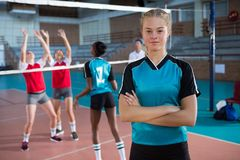 Smiling female volleyball player standing with arms crossed in the court. Portrait of smiling female volleyball player standing with arms crossed in the court Royalty Free Stock Photo