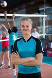 Smiling female volleyball player standing with arms crossed in the court. Portrait of smiling female volleyball player standing with arms crossed in the court Royalty Free Stock Images