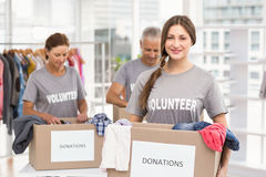 Smiling female volunteer carrying donation box Stock Photo