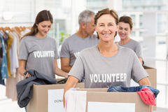 Smiling female volunteer carrying donation box Stock Images