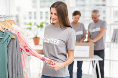 Smiling female volunteer choosing clothes Royalty Free Stock Photo