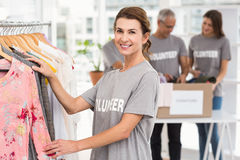 Smiling female volunteer choosing clothes Stock Photos