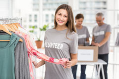 Smiling female volunteer choosing clothes Stock Photo