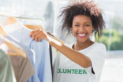 Smiling female volunteer by clothes rack Royalty Free Stock Photography