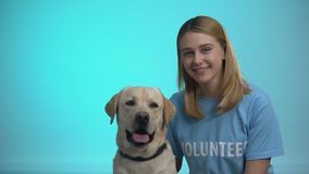 Smiling female volunteer with cute pedigreed dog looking at camera, help animals