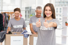 Smiling female volunteer doing thumbs up Stock Photos