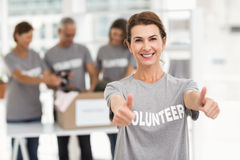 Smiling female volunteer doing thumbs up Stock Image