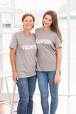 Smiling female volunteers putting arms around each other Stock Images