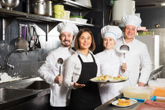 Smiling female waiter collecting dishes from restaurant's kitc Royalty Free Stock Images