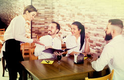 Smiling female waitress taking order from visitors Royalty Free Stock Photos