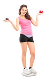 Smiling female on a weight scale holding a red apple and cake Royalty Free Stock Images