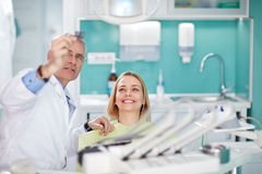 Smiling female woman with dentist looking at dental snapshot. Smiling female women in dental chair with dentist looking at dental snapshot Royalty Free Stock Image