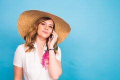 Smiling female woman talking on the phone on a blue background Royalty Free Stock Photos