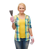 Smiling female worker in gloves with spatula Royalty Free Stock Photography