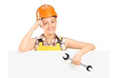 A smiling female worker holding a wrench  Stock Images