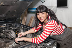 Smiling female worker repairing a car. Smiling woman repairing the car in the garage Stock Photos
