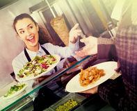 Smiling female worker serving customer. With smile at shawarma place Stock Images