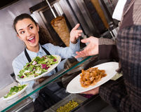 Smiling female worker serving customer. With smile at shawarma place Royalty Free Stock Photos