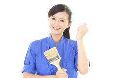Smiling female worker. With a paint brush Royalty Free Stock Photos