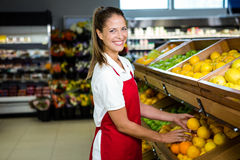 Smiling female worker stocking lemons Stock Photo