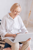 Smiling female working at home. Something interesting. Delighted pensioner woman holding her laptop on the knees and bowing head while looking at screen of her Royalty Free Stock Image