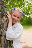 Smiling female in wreath near the tree Royalty Free Stock Photos