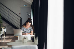 Smiling female writing something in her notebook while sitting at a desk with a laptop. stock photography