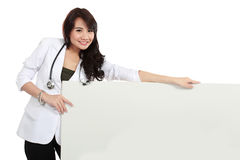 Smiling female young doctor holding blank white board Royalty Free Stock Image