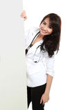 Smiling female young doctor holding blank white board Stock Photography