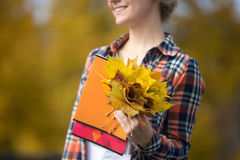 Smiling female young student outdoors holding yellow leaves Royalty Free Stock Photography