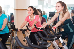 Smiling females of different age training on exercise bikes Royalty Free Stock Photo