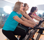Smiling females riding stationary bicycles. In modern gym for women Stock Photo